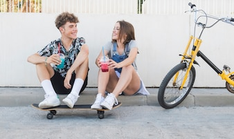 Happy couple with skateboard drinking juice next to bicycle