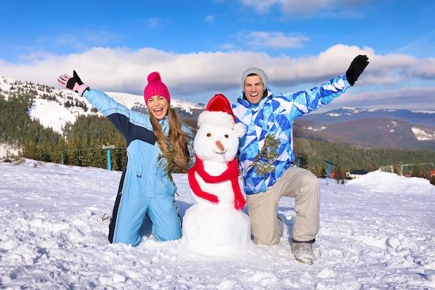 Счастливая пара со снеговиком на горнолыжном курорте. зимние каникулы