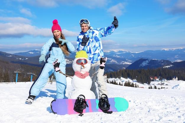 Счастливая пара со снеговиком, весело проводящим время на горнолыжном курорте. зимние каникулы