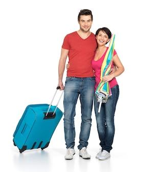 白い背景の上のスタジオに立って、旅行に行くスーツケースと幸せなカップル