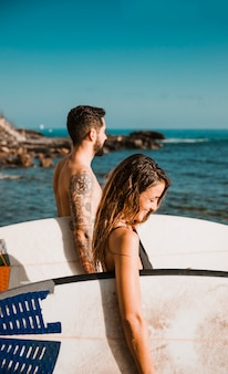 Happy couple with surfboards standing near sea
