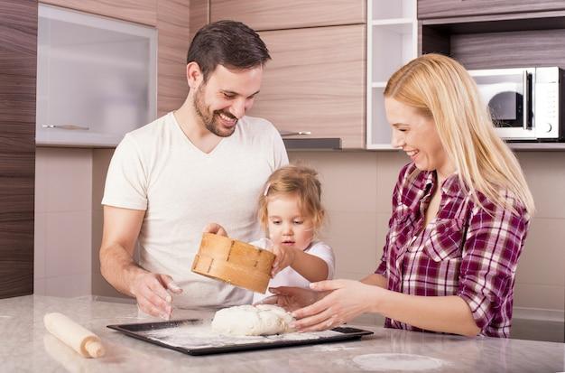 Coppia felice con la loro piccola figlia che cuoce in cucina