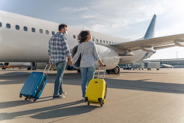 Счастливая пара с дорожными сумками, идущая по аэродрому