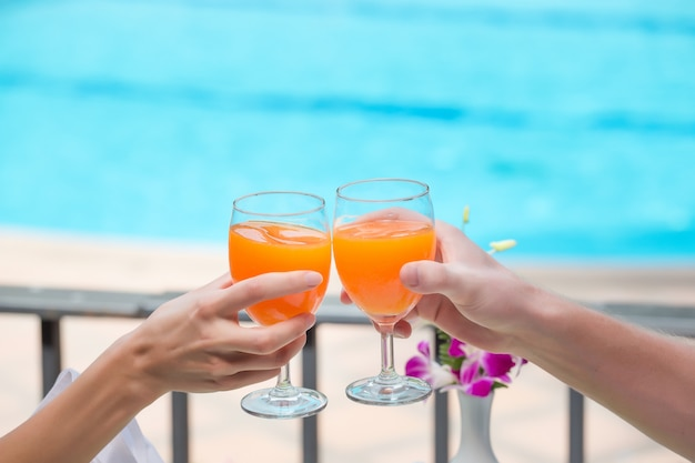 Happy couple with two glasses of orange juice at swiming pool vacation