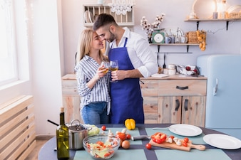 Happy couple with wine glasses hugging in kitchen