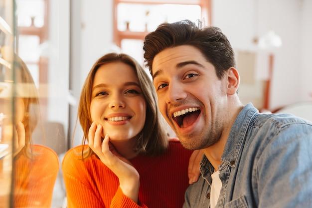 Счастливая пара женщина и мужчина улыбаются и радуются, отдыхая в уютной пекарне