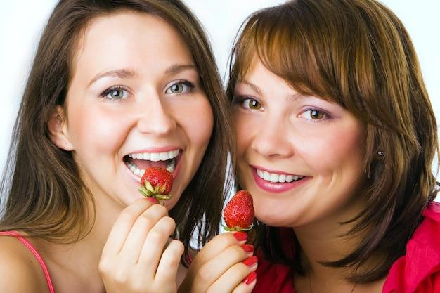 幸せなカップルの女性は白でイチゴを食べる