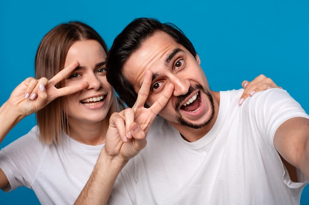 Happy couple of a young blond woman and brunet bearded man with mustaches in white t-shirts and blue jeans making selfie nd. concept of an ideal couple.