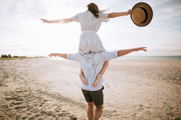 Happy couple. young woman on her husband's shoulders on the beach. summer vacation concept