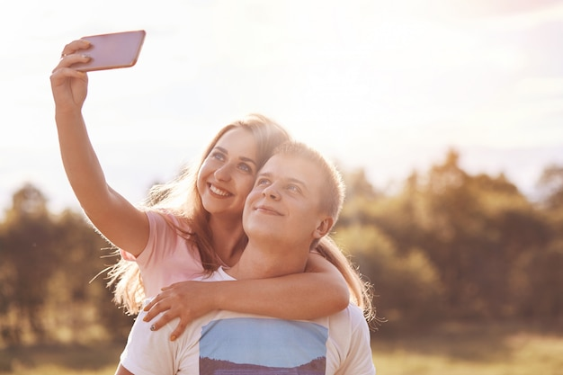 Happy couple of youngsters embrace, makes selfie shot while recreate outside during sunny day