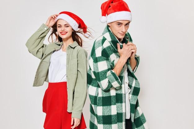 행복한 커플과 축제 모자와 밝은 옷을 입은 여성 크리스마스 새해