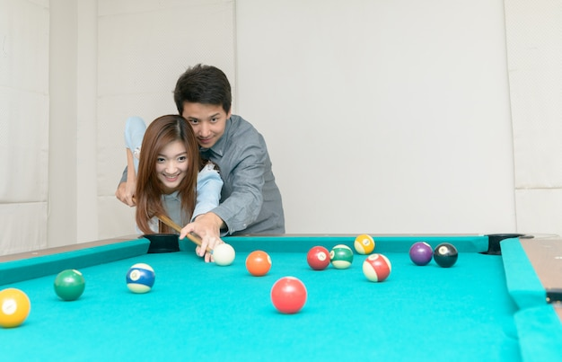 Happy couples are playing billiards in home,