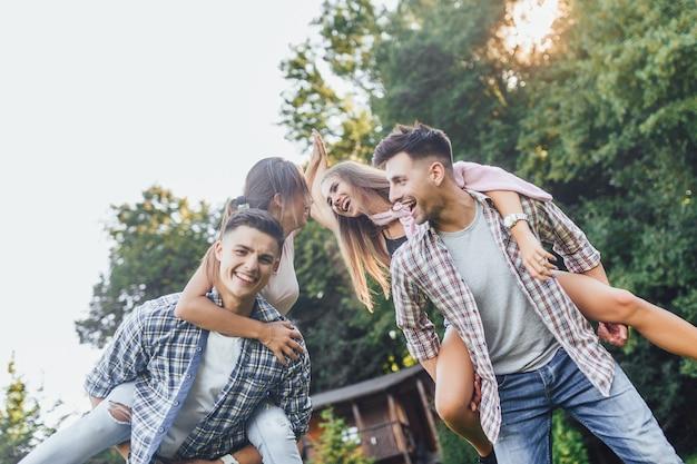 公園で幸せなカップル。女の子を肩に乗せた男の子、太陽が輝いています。