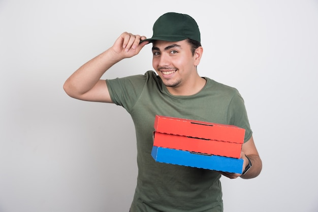 Happy courier holding three boxes of pizza and his cap on white background.