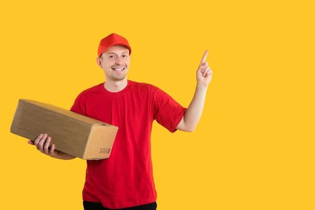 赤い制服を着た幸せな宅配便は、コルトンボックスを保持し、黄色の空きスペースに指を向けます