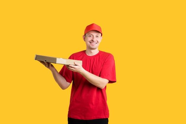 赤い制服を着た幸せな宅配便は、黄色の手でピザを保持します