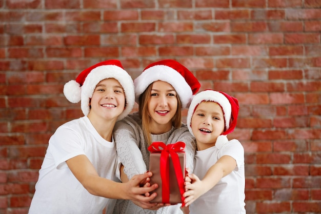 Happy cousins with gift box on brick wall background