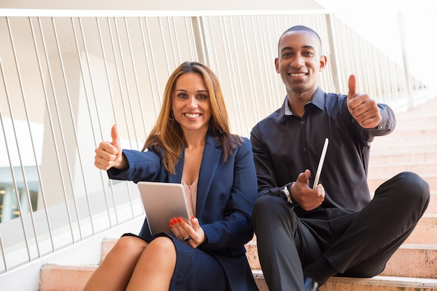 Happy coworkers holding tablets and showing thumbs up on stairs