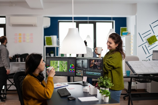 Happy coworkers talking about film montage looking at movie footage working in creative start up agency office with two monitors