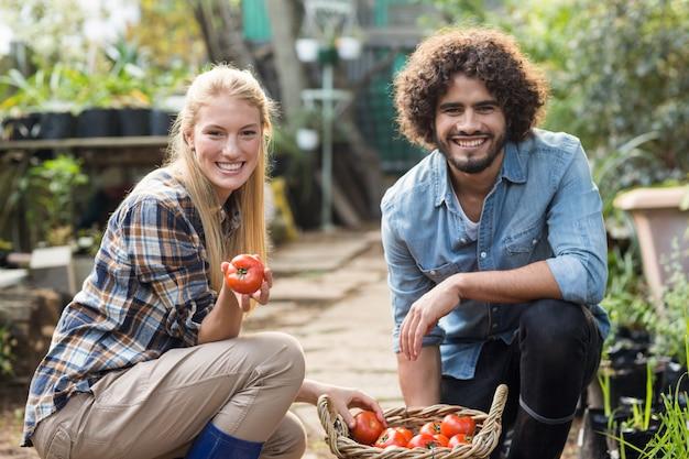 Счастливые коллеги с томатной корзиной