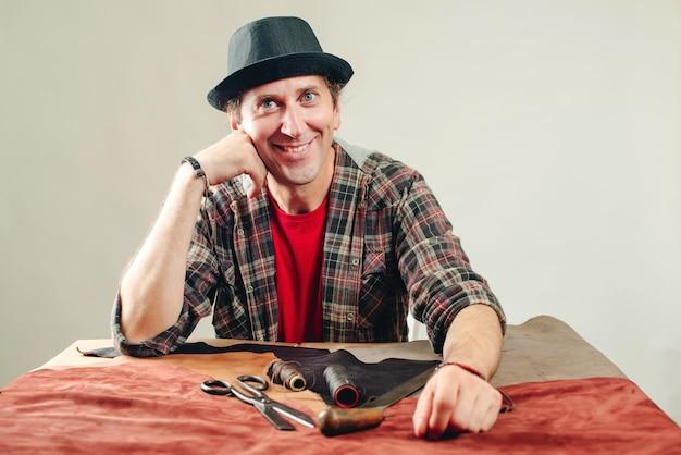 Счастливый мастер на рабочем месте. работник создает новое изделие из кожи в мастерской. инструменты для крафта, кожа на столе. ручной инструмент. малый бизнес