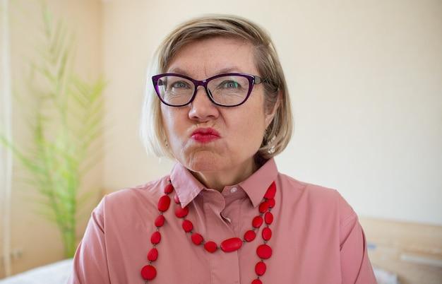 Счастливая сумасшедшая модная старшая женщина седые волосы старшая женщина, зрелая женщина средних лет, улыбающаяся старуха в бусах на светлом фоне, позитивная одинокая женщина-пенсионерка