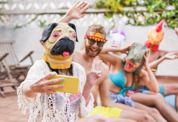 Happy crazy friends having fun taking selfie and party masks sitting next swimming pool