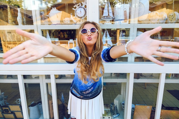 Happy crazy pretty woman put her hands to the front, and send you kiss. posing near souvenir ship in bright casual clothes and sunglasses. funny bright image of girl having fun.
