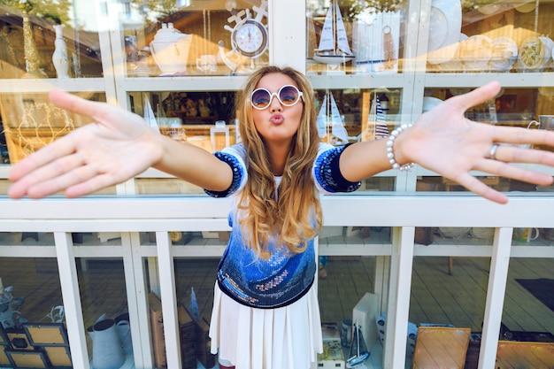 행복한 미친 예쁜 여자가 손을 앞으로 내밀고 키스를 보냅니다. 밝은 캐주얼 옷과 선글라스에 기념품 배 근처 포즈. 여자 재미의 재미있는 밝은 이미지.