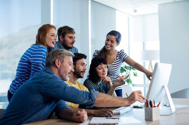 사무실에서 데스크탑 pc에서 함께 작업하는 동안 논의하는 행복 창조적 인 비즈니스 팀