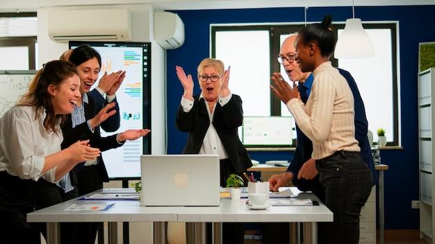 브로드룸 사무실에서 회의를 하는 행복한 창의적인 비즈니스 팀. 계약을 체결하는 성공적인 거래를 축하하는 비즈니스 파트너. 긍정적인 감정을 가진 기업인의 인종 간 그룹입니다.