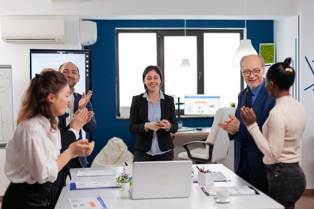 ブロードルームオフィスでの会議で幸せなクリエイティブビジネスチームが大喜び