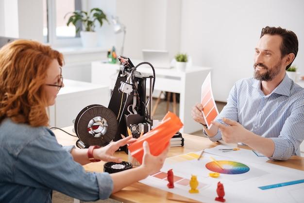 오렌지색을 가리키며 동료와상의하면서 선택 하자고 제안하는 행복한 창의적인 남성 디자이너