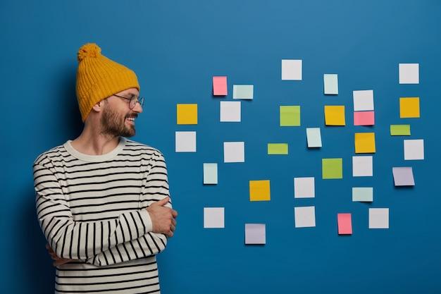 幸せな創造的な男性のフリーランスの労働者は、手を組んで立って、黄色い帽子とストライプのジャンパーを着て、作業場所で右側のスタンドを見て