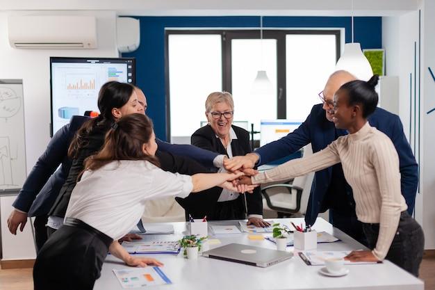 成功したプロジェクトを祝う幸せな創造的な多民族のビジネスチーム