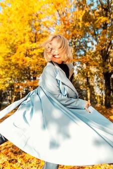 ファッショナブルなコートを着た若い笑顔の美しい面白い女の子の幸せな創造的な肖像画は、明るい色の葉のある秋の公園で動きを歩きます。女性の喜びと前向きな感情