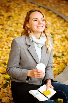 Happy creative woman with paper notebook and coffee drink outdoors in autumn park with golden leaves