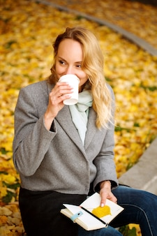 Happy creative woman with paper notebook drinking coffee outdoors in autumn park with golden leaves