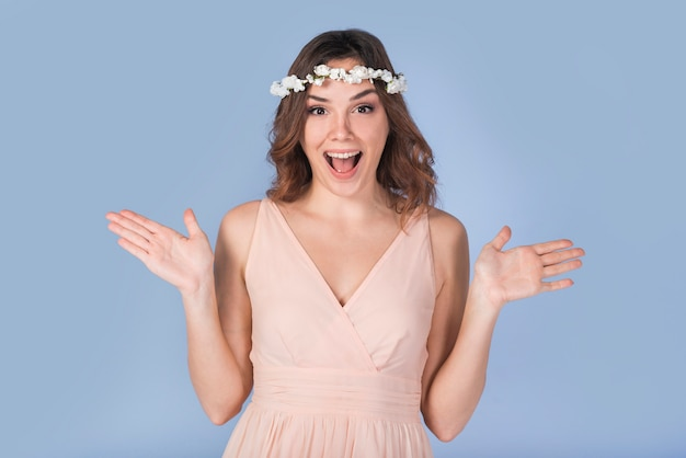 Happy crying young lady in dress with white wreath on head