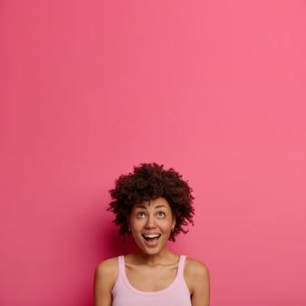 행복한 호기심이 흥분된 여자는 위쪽으로 시선을 유지하고, 즐거운 표정으로 바라보고, 매력적이고 흥미로운 것을 발견하고, 분홍색 벽에 포즈를 취합니다. 텍스트 또는 홍보를위한 공간 복사