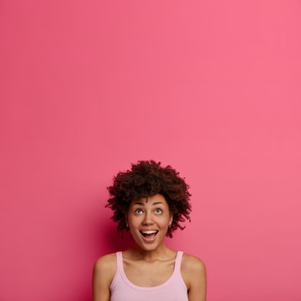 Happy curious excited woman keeps gaze upwards, looks up with joyful expression, notices something appealing and interesting, poses against pink wall copy space for your text or promotion