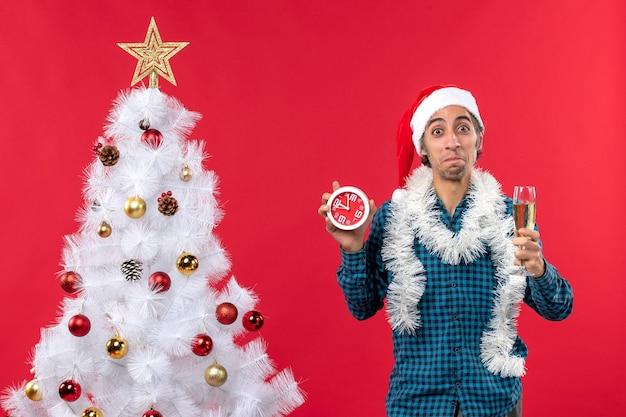 サンタクロースの帽子をかぶって、グラスワインを上げて時計を持っている幸せな好奇心旺盛な若い男