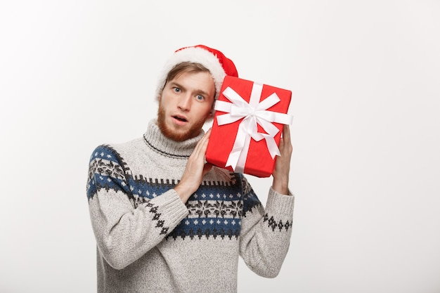 Il giovane curioso felice con la barba trasporta il presente e ascolta all'interno della scatola isolata su bianco