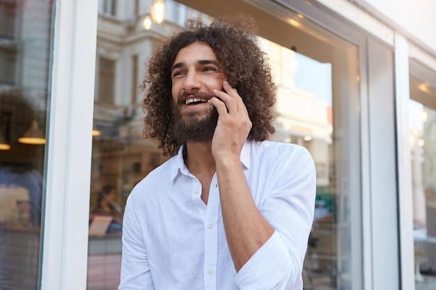 Ragazzo barbuto riccio felice che cammina per strada e parla piacevolmente sul suo telefono, guarda avanti e sorride ampiamente, indossa una camicia bianca