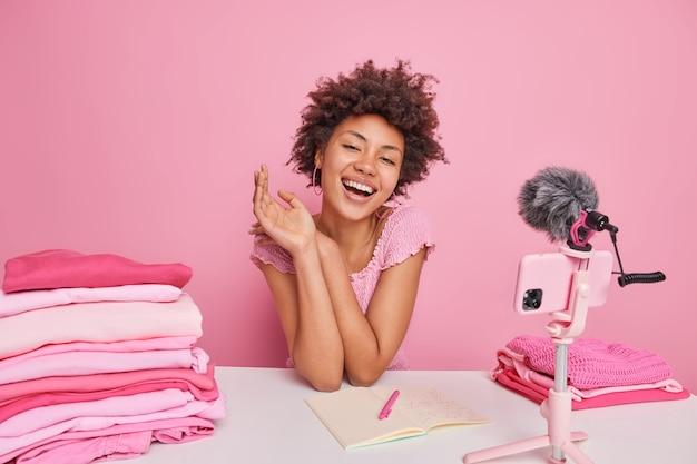 幸せな巻き毛の女性ブロガーは、新しいコンテンツについて考えます笑顔は、ノートブックの折り目に情報を心地よく書き留めます洗濯物はピンクで隔離されたスマートフォンのウェブカメラを使用します