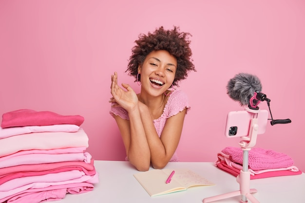 Happy curly female blogger thinks about new content smiles pleasantly writes down information in notebook folds laundry uses smartphone webcam isolated over pink
