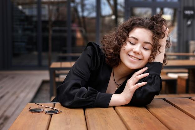 검은 재킷에 행복 곱슬 소녀 미소와 거리에 나무 테이블에 앉아