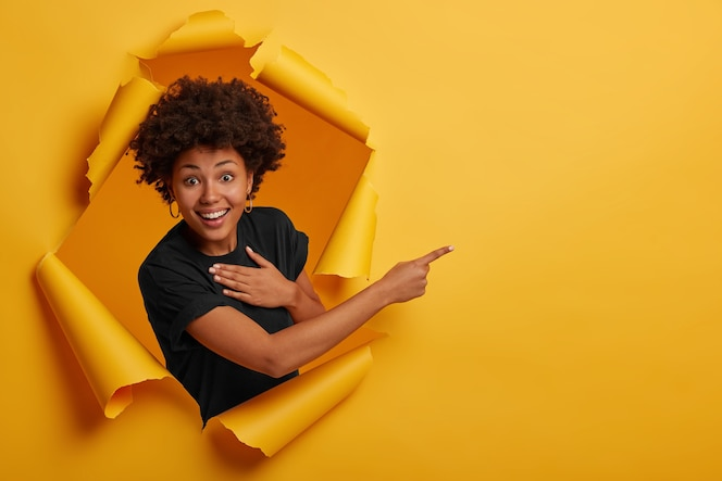 Happy curly haired african american woman laughs positively, points aside on copy space, wears black t shirt