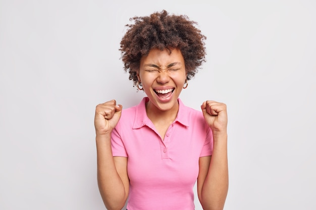 Happy curly haired afro american woman makes fist pump rejoices positive results wears casual pink t shirt