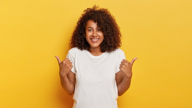 Happy curly haired girl makes thumbs up sign, demonstrates support and respect to someone, smiles pleasantly , achieves desirable goal, wears white t shirt, isolated on yellow wall